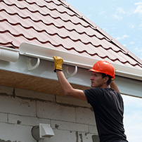 Worker Using Gutter Hangers to Install Rain Gutter System