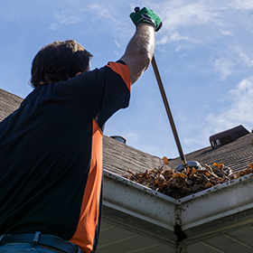Man cleaning a clogging rain gutter installation