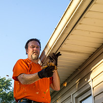 Man cleaning up installed rain gutters in fall