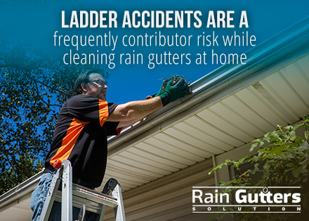 Man cleaning rain gutters at home